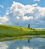 Reflection of the sky with clouds in the water near the green hill Royalty Free Stock Images