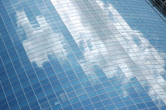 Reflection of sky in glass fac. Blue sky and clouds reflected in the glass facade stock image