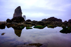 Reflection of Sky and Rocks in Tide Pools. Afternoon sun through the seashore misty haze reflects mirror images of the rocks and clouds in still water of tide royalty free stock photos