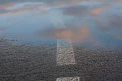 Reflection of the sky in the wet asphalt and puddle after the rain, in the setting sun. Road marking going into the water. Close u Royalty Free Stock Photos