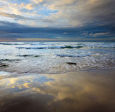 Reflection of sky on wet sand and waves at Borneo, Sabah, Malaysia Stock Images
