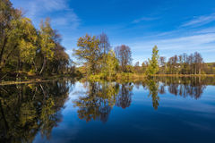 Reflection of small trees in a lake under a blue sky with intermittent clouds Royalty Free Stock Photos