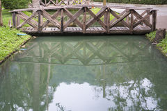 Reflection of the small wooden bridge in the mirror smooth Royalty Free Stock Photos