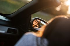 Reflection of a smiling young dark-haired girl in sunglasses in a side mirror of a car. royalty free stock images