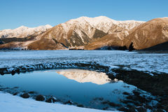 Reflection of snow-covered mountain in small pond Royalty Free Stock Photo