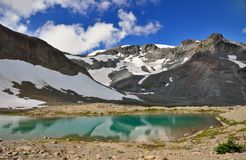 Reflection of snowy mountains in a lake in Mount Rainier Stock Images