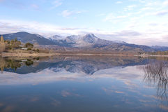 Reflection of the snowy mountains on the lake. Reflection of snow covered mountains on calm lake in a beautiful and sunny winter sunset Royalty Free Stock Photography