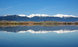 Reflection of snowy Rohace mountains. Spring view of snowy hills of Rohace mountains mirrored in deep waters of Liptovska Mara lake located in Liptov region royalty free stock photography