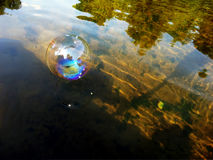 Reflection in the soap bubble floating down the river Royalty Free Stock Photo