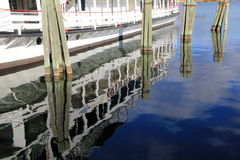 Reflection of steamboat and wood pilings on calm water Stock Photography