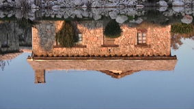 Reflection of stone house on water stock footage