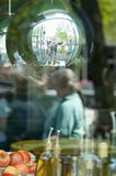 Reflection of the street in a mirror ball hanging in a glass window royalty free stock photo