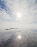 Reflection of the sun on a misty lake. Stock Photos