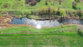 The reflection of the sun in the river. Aerial view of the river. Spring meadows and trees on the river bank stock footage
