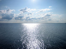 Reflection of sun in the water on blue sky background, horizontal view. Reflection of sun in the water on blue sky background, horizontal view Royalty Free Stock Photography
