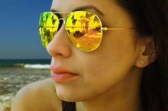 Reflection in sunglasses on the girl, beach. Royalty Free Stock Image