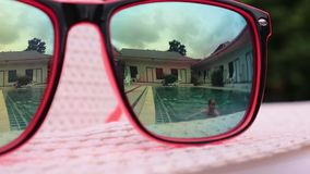 Reflection in sunglasses of pretty happy woman jumping into the pool. concept of summer holidays.  stock footage