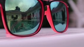 Reflection in sunglasses of pretty happy woman jumping into the pool. concept of summer holidays.  stock video