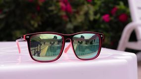 Reflection in sunglasses of teenagers girl enjoy in hotel swiming pool in vacation. two sisters playing, swimming and. Jumping in water stock video footage