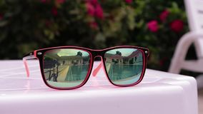 Reflection in sunglasses of teenagers girl enjoy in hotel swiming pool in vacation. two sisters playing, swimming and. Jumping in water stock video