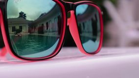 Reflection in sunglasses of teenagers girl enjoy in hotel swiming pool in vacation. two sisters playing, swimming and. Jumping in water stock footage