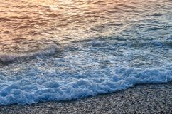 Reflection of sunlight on the surface of the sea. And sea foam near shore Royalty Free Stock Photography