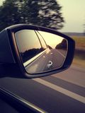 Reflection of sunny road at the car side mirrow. Rear view mirro royalty free stock images
