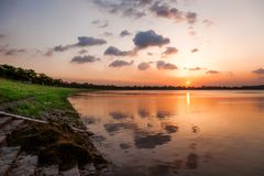 Sunset at distant edge of Lake. Reflection of Sunrise and clouds over the lake and beach Stock Image