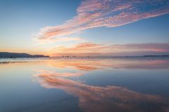 Reflection sunrise or sunset view with orange cloud and blue sky Stock Photos