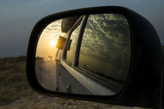 Reflection of sunset in a car mirror. Reflection of a safari jeep and the sunset in the mirror of a car. Clouds reflected in the window of the car Stock Photography
