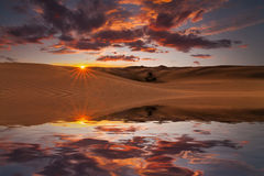 Reflection of the sunset sky and dunes in the water. Royalty Free Stock Photo