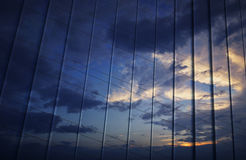 Reflection of sunset sky in metal wall of office tower Stock Images