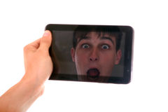 Reflection in Tablet Computer. Reflection of Surprised Face in Display of Tablet Computer Isolated on the White Background Royalty Free Stock Photo