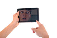 Reflection in Tablet Computer. Reflection of Surprised Face in Display of Tablet Computer Isolated on the White Background Royalty Free Stock Photography