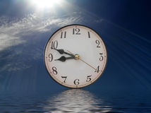 Reflection Time. Clock with reflection on rippling water - concept of taking time out to reflect on life Royalty Free Stock Images