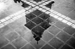 reflection of a tower in a water pond stock photo