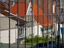 Reflection of traditional Norwegian houses in windows of modern building Royalty Free Stock Photography