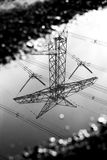 Reflection of transmission tower in a puddle Royalty Free Stock Photography
