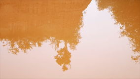 Reflection of tree and hill in orange water. From digging soil horizon stock video