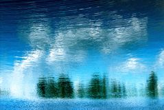 Reflection of trees. Rippling reflection of trees and blue sky in water Royalty Free Stock Images