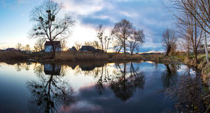 Reflection of trees and hauses in river at dawn. Reflection of trees and hauses Royalty Free Stock Photography