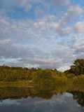 Reflection of trees on riverbank Royalty Free Stock Images