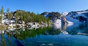 Reflection of trees and rocks in clear water. Royalty Free Stock Photos