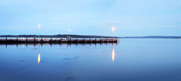 Reflection of Twilight on Lake with pier. A gorgeous blue stillness with pier on lake at twilight Stock Photography