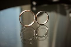 The reflection of two wedding rings in the glass stock images