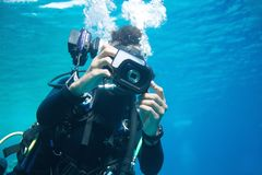 The reflection of an under water photographer`s subject is reflected in the lens of his camera royalty free stock photo