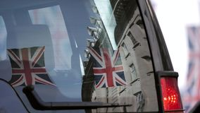 Reflection of Union Jack Flags on Regent Street a day before Royal Wedding. Between Prince Harry and Meghan Markle will be held at Windsor Castle in Berkshire stock footage