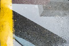 Reflection of an urban building on a puddle of water on the street, yellow line parking place royalty free stock image