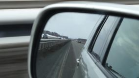 Reflection view of road in side rearview mirror of a car stock footage