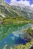 Reflection of Vihren peak in Okoto lake, Pirin Mountain Stock Images